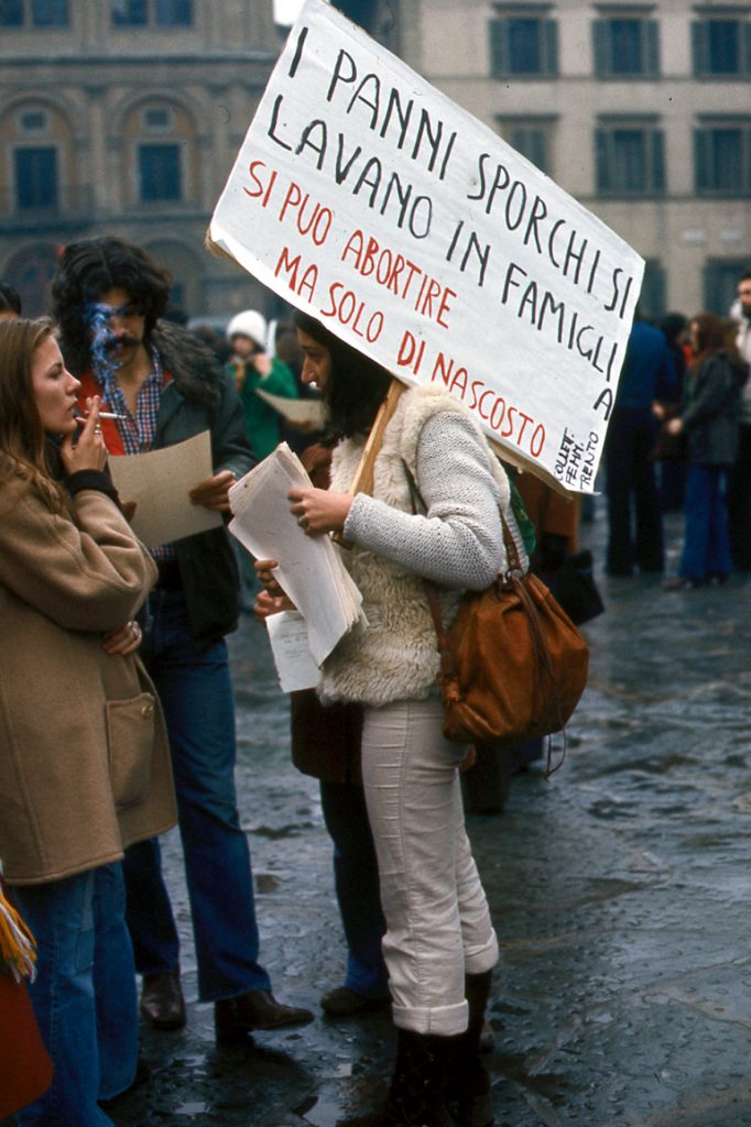"""A woman at an Italian feminist demonstration in the 1970s carries a sign reading, """"Dirty laundry stays in the family. You can have an abortion but only in secret."""""""